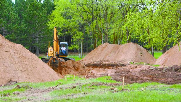 Pictured, Phil Bjerga digs the basement for the home, which will be built by Derek Holst Construction.