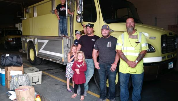 Motley firefighters Bryan Stevens  (left) and Nick Dille (center) packed up and made preparations at the fire hall Sept. 14, the evening before departing for Oregon to help battle the wildfires across the state. They are pictured with Motley Fire Chief Brad Olson (right); and Stevens' children who stopped by to offer their dad some support and a few hugs along the way. The Stevens children, from left, are Ben, eight; Gavin, 11; Brynn, seven; and Kallyn, four. Dille's sons, Easton, five, and Lonny (Bubba), t