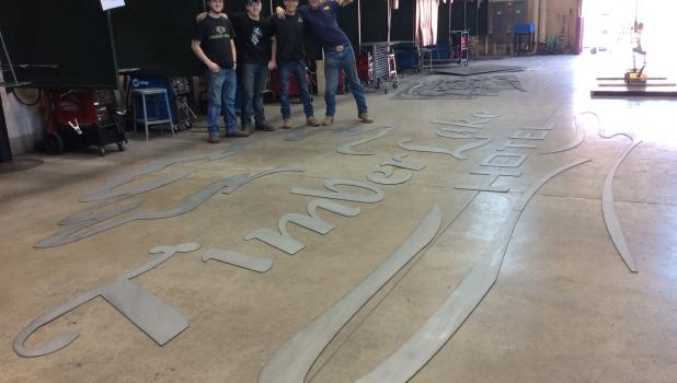 CLC students Nicholas McCullough, Corbin Hendrickson, John Raboin and Ryan Hamann look over the parts of the sign they created for the Timberlake Hotel in Staples. (Submitted photo)