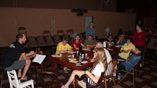 "Matthew R. Olsen, director for the play, ""Twelve Angry Men,"" gives the cast some feedback during a recent rehearsal in Wadena. The play is being co-produced by Lamplighter Community Theatre in Staples; and Madhatters Community Theatre in Wadena. It opens Thursday, Aug. 11, at Centennial Auditorium in Staples. Cast members pictured clockwise around the table are Kevin Olsen, Tamber Edin, Paul Baymler, Jerry Reck (standing), Mim Maas, Pam Collins, Carol Aspengren, Meg Litts (standing), Hallie Olsen, Don Hoffm"