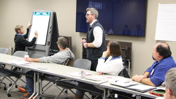 At the manufacturing cluster meeting, Pillager High School teachers Jordan Herman (left) and Kevin Votaw explain their Metier Program that helps students discover how and when they do their best work.