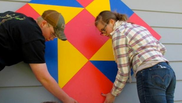 FFA students Brenden Thompson and Bekka Paskewitz help Tom Kajer secure the Friendship Star barn quilt to the house.