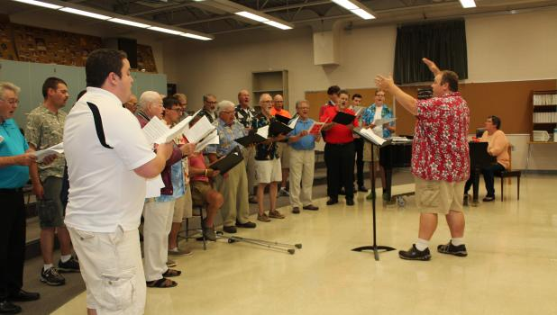 Rob Freelove (right) has been selected as the new director of the Staples Area Men's Chorus. Here he rehearsed the chorus prior to their appearance at the Little Red Caboose Variety Show during Railroad Days. (Staples World photo by Brenda Halvorson)