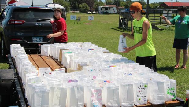 Nick Niemi, right, places luminaria bags onto a trailer to disperse along the walking trail for tor the Relay For Life on July 22. Each bag is dedicated to someone who has survived cancer or in memory of someone who has died because of cancer.