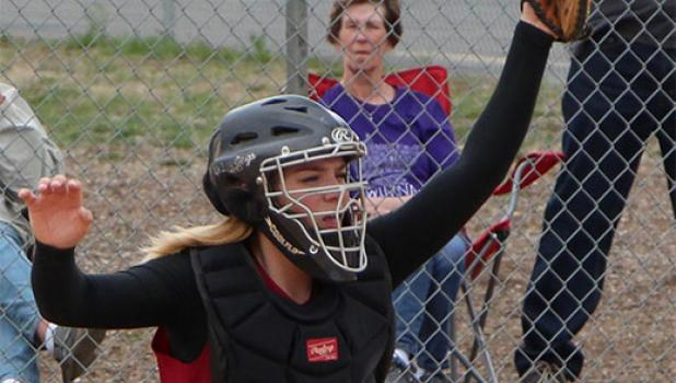 Cardinal softball catcher Riley Peterson holds on to a high pitch behind the plate.
