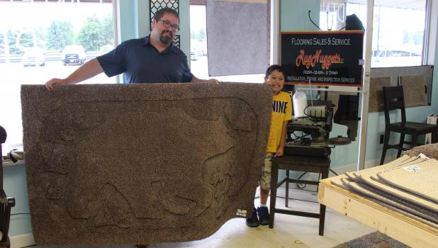 Cale Simkins and his son Allen hold a bear rug Simkins created with a rug binder, pattern and scissors. The new store, Rug Nuggets, is located along Highway 10, between 4th and 5th Street NE. On the chair next to Allen is the binding machine that Simkins purchased and fixed up after finding the family owned company that built the machine. (Staples World photo by Mark Anderson)