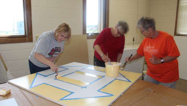 Three members of Barn Quilts of Central Minnesota put the first coat of paint on a 4 ft. by 4 ft. barn quilt which will eventually be installed at Don and Dave's Store. From left are Lisa Kajer, Pam Collins and Mary Noska.