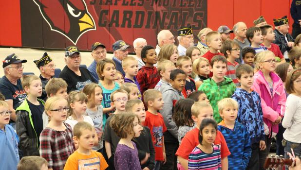 """Staples-Motley Elementary students honored the veterans at the Veteran's Day Program held Nov. 11, with singing, """"This Land is Your Land"""" for the crowd and the veterans seated behind them."""