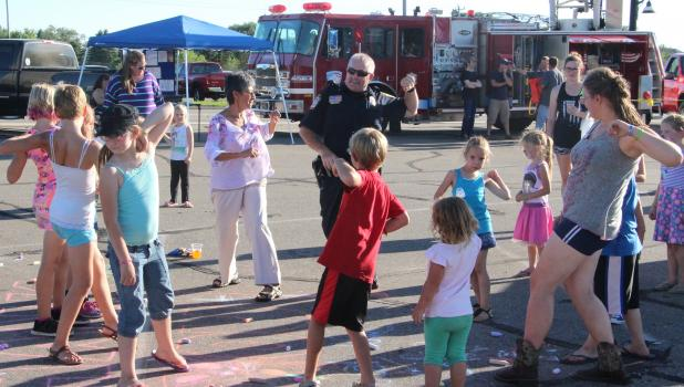 """Motley Police Chief Ron Smith led a group dancers in the """"Hokey Pokey"""" at National Night Out Aug. 2 in Staples."""