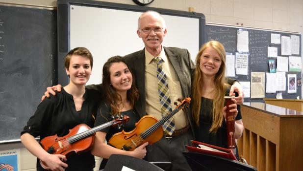 """Pictured above with retiring band director Jeff Iverson are, from left, seniors Anna Koopmann, Josie Erickson and Jenessa Iverson, who performed """"Four London Trios."""" This was the last group to perform at Jeff Iverson's final contest and they had a perfect score of 40."""