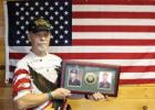 From army to local veteran advocate Charlie Poulton at his home south of Staples, holding the plaque he received after retiring from the U.S. Army, showing a photo when he entered the army before Vietnam and when he retired after 34 years in the service. He now acts as a veterans coordinator with Lakewood Health System and is a member of the Staples All Veterans Park Board. (Staples World photo by Mark Anderson)