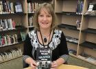 Angie Johnson, Library Assistant at the Staples Public Library, holds one of the books by Chad Lewis about haunted locations in Minnesota. Lewis will present a program on his research at the library from 6:30-7:30 p.m., Tuesday, Jan. 9. He has co-authored Road Guide books for several other states as well as books about gangsters and mysterious creatures. (Staples World photos by Brenda Halvorson)