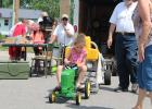 Amaya Baker, four, of Brooklyn Park, was one of several contestants at the Kiddie Tractor Pull during Motley's June Fest. Amaya attended the event with her grandma, Sue Griffith of Staples. In the background is emcee Marge Tepley, who owns CT Pedal Pull along with Bob Cheney, both of Motley. (Staples World photo by Dawn Timbs)