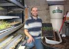 Russell Kleinschmidt, rural Staples, owns and operates Kleinschmidt Farms, a CSA (Community Supported Agriculture) farm. He and his wife, Jessica, sell over 60 varieties of garden produce, all started from seed. Kleinschmidt mixes his own potting soil and plants the seeds in 20-row seed flats kept under lights in his basement. He is pictured on March 20, with seeds that have begun to sprout and will be transplanted in the near future. (Staples World photo by Dawn Timbs)