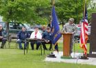 Above left, Larry Doucette, right, gave credit to the veterans no longer with us during his Memorial Day address to the crowd gathered at Evergreen Hill Cemetery in Staples May 29. Seated, from left, are Don Amundson, Arlene Grover and Huck Holst. (Staples World photo by Mark Anderson)