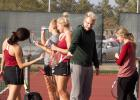 Coach Nathan Thelen discusses strategy with doubles players at the section meet.