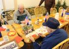 Dean Fearing of Staples, left and Robert Warnberg of Princeton, right look at photos of past reunions of crew members of the USS Lowndes. The two, who are former shipmates met Nov.22, at Fearing's home in Staples. (Staples World photo by Mark Anderson)